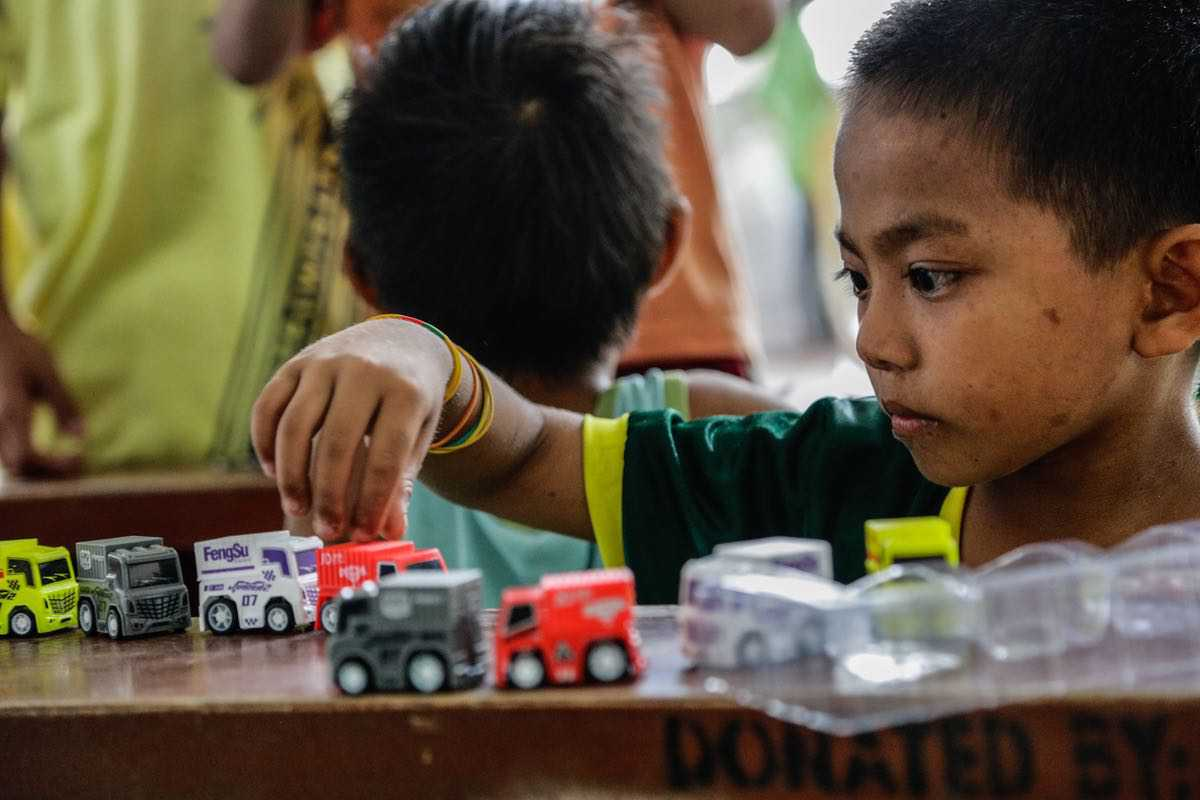 After the noise of Mount Taal's eruption, this little boy spends some quiet time while playing with his new toy cars.