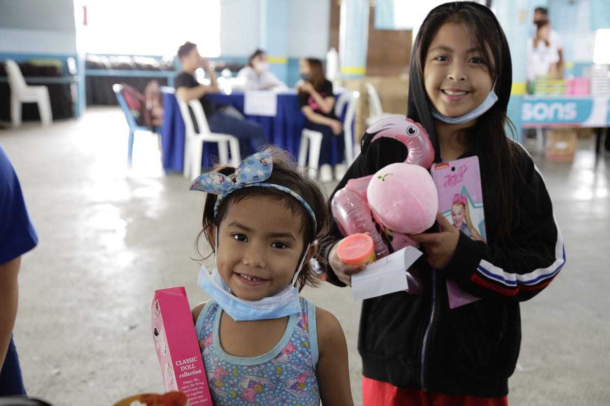 These little girls are all smiles as they receive their new toy packs from The SM Store.