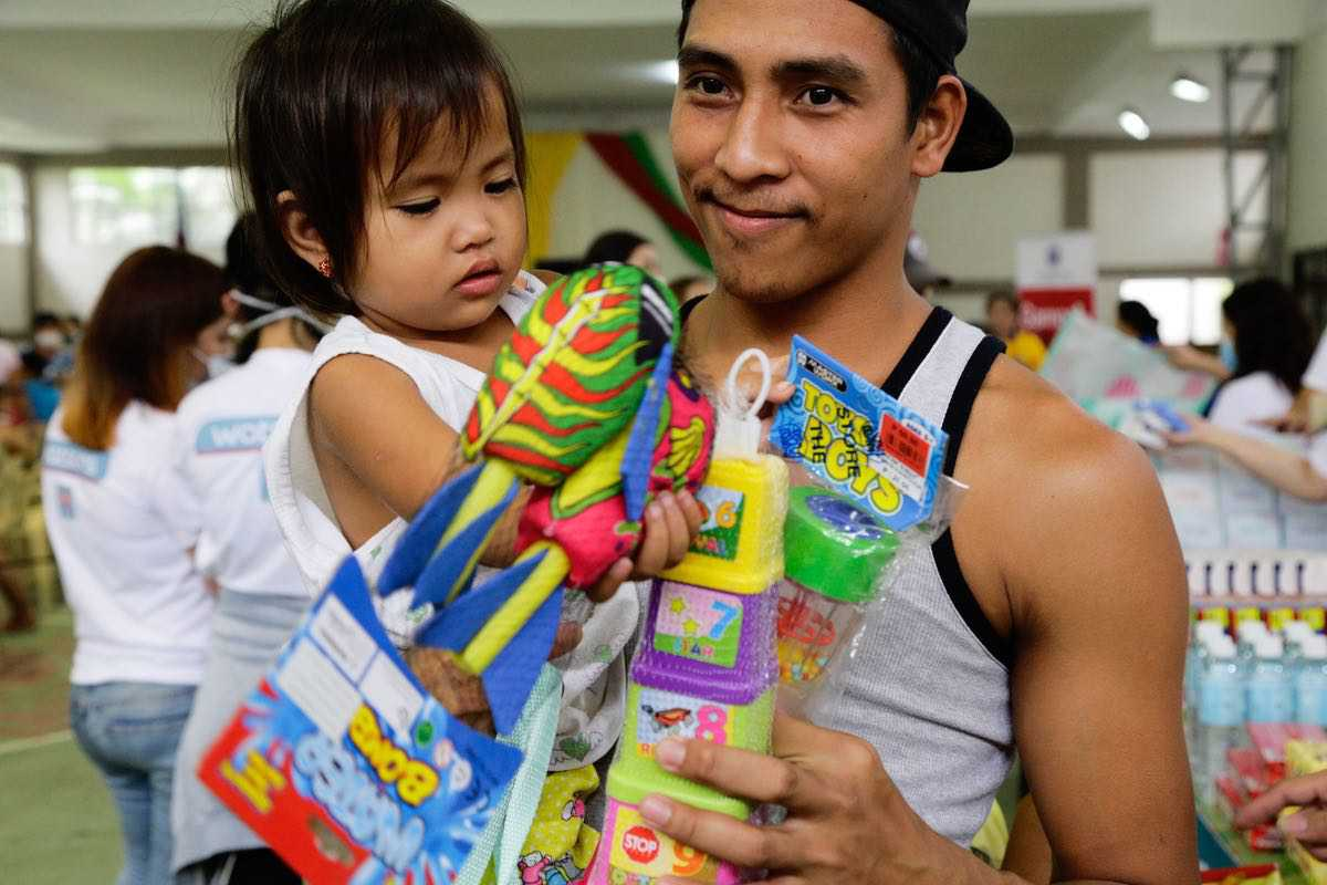 This little boy carried by his father received educational toys from The SM Store's Share the Magic of Giving, Donate-a-Toy campaign.