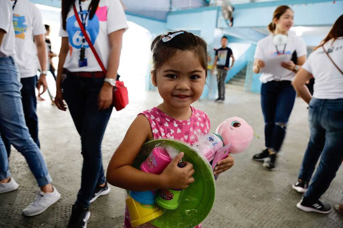 All smiles and ready to play, this little girl is excited with her new Play Doh sets and plush toy.